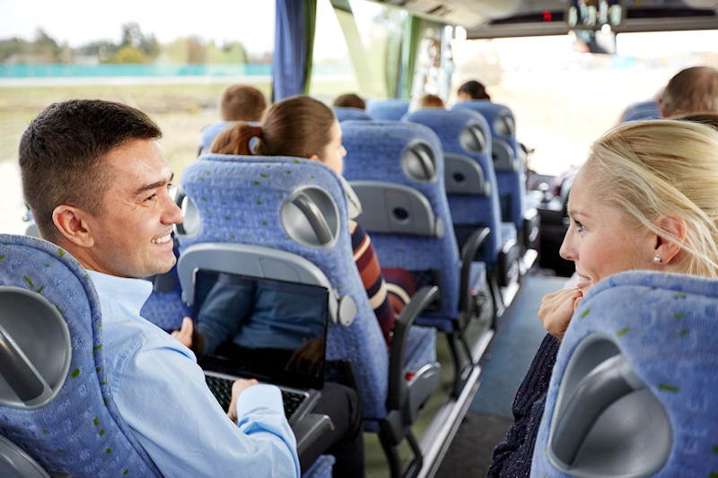 Couple looking a iPad on a group tour bus