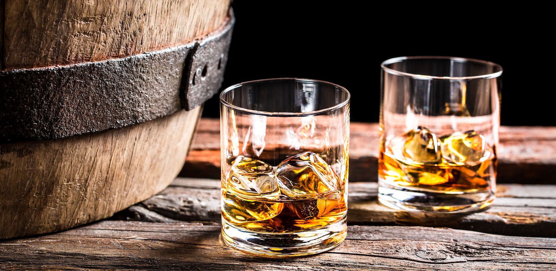 Bourbon glasses sitting next to a bourbon barrel