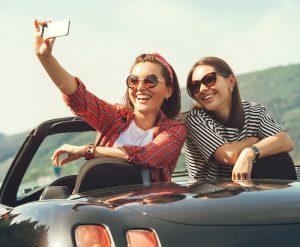 Girlfriends taking selfie in convertable