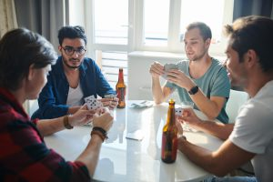 Group of guys playing poker and drinking beers