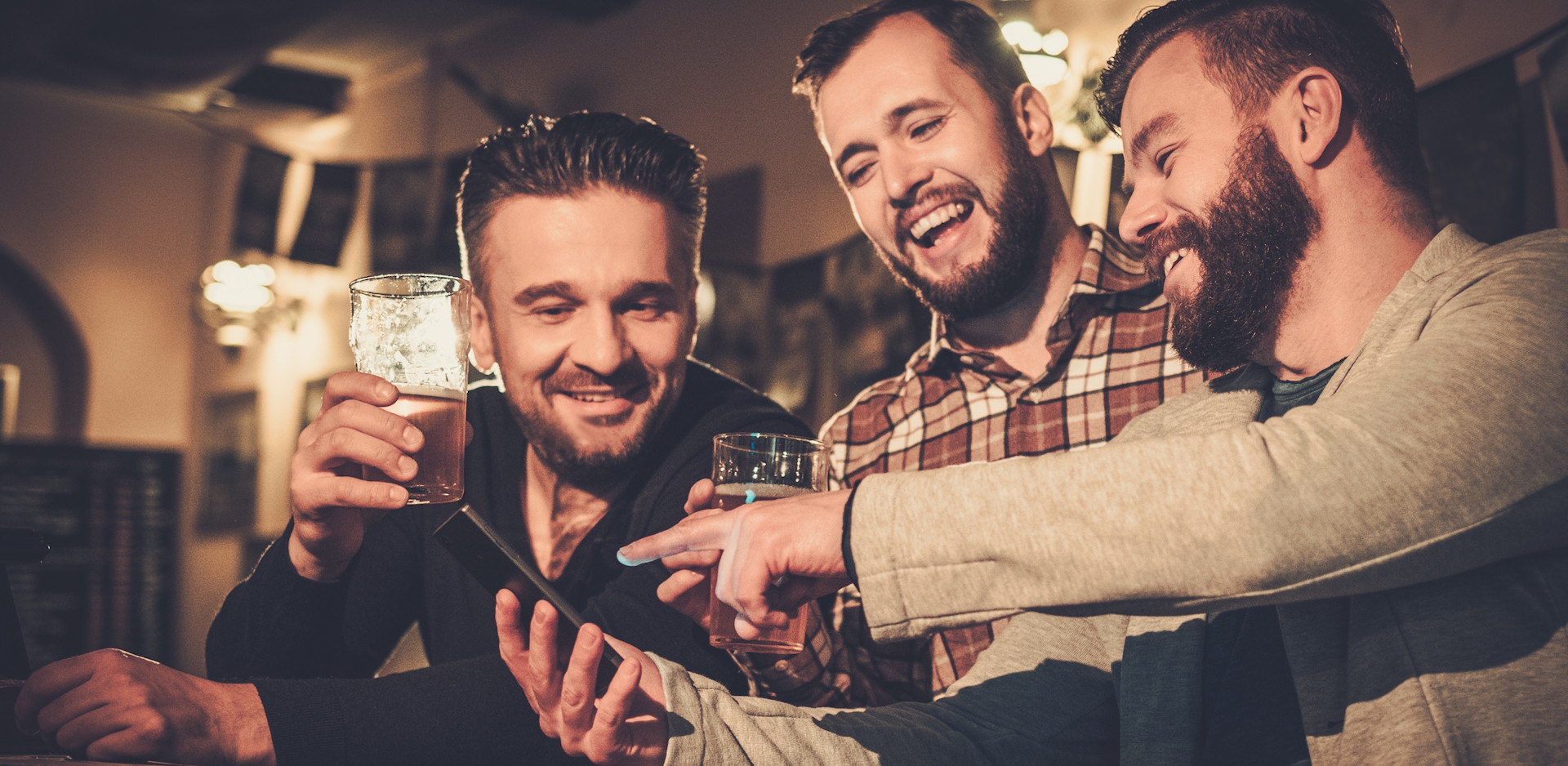 A bunch of guys hanging out having a good time and drinking beer