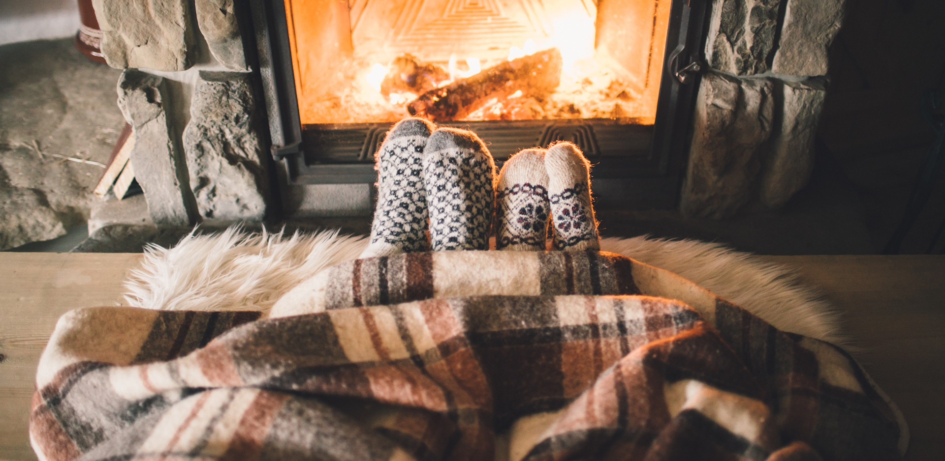 Couple snuggled up with blanket and warm socks in front of fireplace